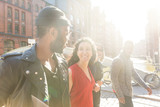 Mixed race group walking in Hamburg, Germany. Four persons, with different ethnicities and wearing urban style clothes, looking each other and smiling. Lifestyle and friendship concepts