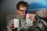 Sick man blowing his nose in the tissue, sick man snotty drinking warm healing tea