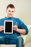 Young man with tablet showing copy space