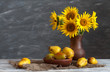 Still life: a set of pottery, a bouquet of sunflowers and pears on a wooden table. Natural light from the windows.