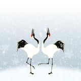 雪の中で求愛ダンスをするタンチョウ鶴のカップル