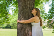 Happy woman hugging a tree in the forest