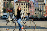 Cute girl in a striped cardigan with bicycle on the street of the ancient city. Sunny warm day.