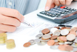 Tax calculation or new loan agreement with hand calculator and coins