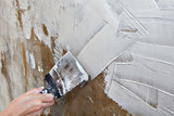 Aligning wall painters putty, painter hands holding steel spatul - 121756666