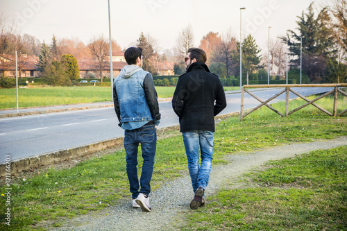 Two handsome casual trendy young men, 2 friends, in an urban park walking and ch Poster