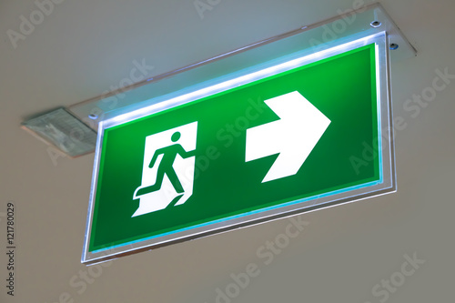 Poster green emergency exit sign showing the way to escape
