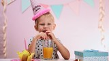 Lovely blond girl drinking orange juice through straw at birthday party. Concept of anniversary celebration and holidays.