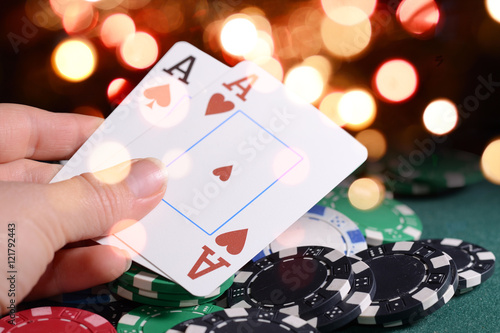 Poster Casino chips and pair of aces in a croupier's hand against bright bokeh lights