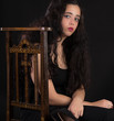 Portrait of young woman sitting on an old chair with shoes in hand.