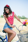Young beautiful brunette pinup woman cycling in fields under bright blue summer sky copy space image