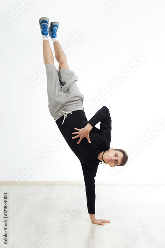 Plexiglas Hip hop dancer performing isolated over white background. Hip hop performer is standing on the hand.