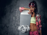 A woman posing with a snowboard on grey background.