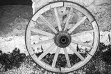 Old wooden wheel stands near rural wall