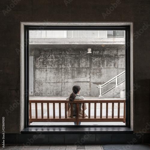 Poster mulher através de janela pensa sobre a vida