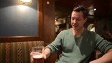 Happy man drinking beer at pub