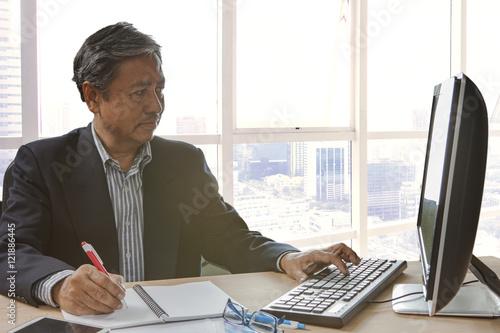 Poster senior asain business man writing and working on pc computor