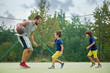 Young children, brothers and their father, playing basketball