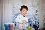 Cute little preschool boy, drawing picture on mug for his father
