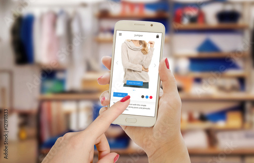 Online shopping with smart phone on e commerce web site or app. Clothing store in the background.