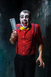 The scary clown holding a knife on dack. Halloween concept