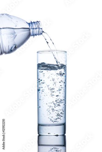 Drinking water is poured into a glass from bottle