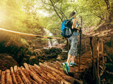 Fototapety Hiking. Woman hikers walking on a bridge on the forest in the mountains on the waterfall. Girl with a backpack and sneakers traveling outdoors. Adventure in a hike.