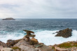 Inukshuk and surf at the coast of Newfoundland