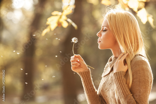 Beautiful blond hair woman relaxing the park on beautiful autumn day.She blowing a dandelion.