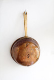 Old style copper colander on aged white wall background. Retro kitchen utensils hanging on a hook. vertical