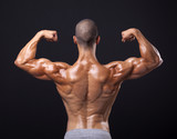 Back view of a male bodybuilder flexing his biceps on black back