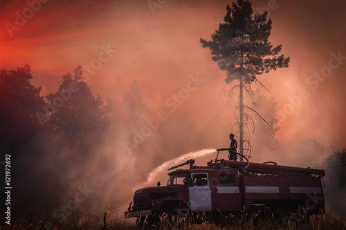 strażak gasi pożar o zachodzie słońca