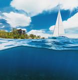 Catamaran boat sailing next to tropical island