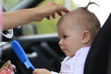 Sad baby in the car and the womans hands are making the hair st