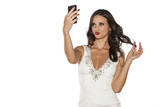 elegant young woman takes selfies with her phone