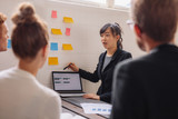 Young female executive giving presentation to coworkers