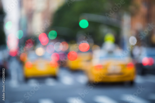 Yellow taxis crowd the streets of New York City at dusk in a defocus abstract scene of green traffic lights and red tail lights