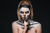 Portrait of woman with gothic skeleton makeup showing silence gesture