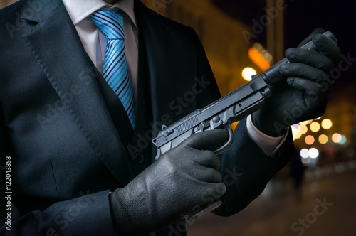 Hitman or assassin holds pistol with silencer in hands. Poster