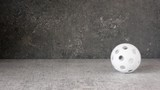 White floorball rolling and bouncing in slow motion