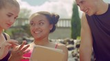 Happy friends surf internet on tablet outdoor. Closeup of young people having fun together with tablet computer. Happy people smiling looking at tablet. Multiracial friends using tablet in park