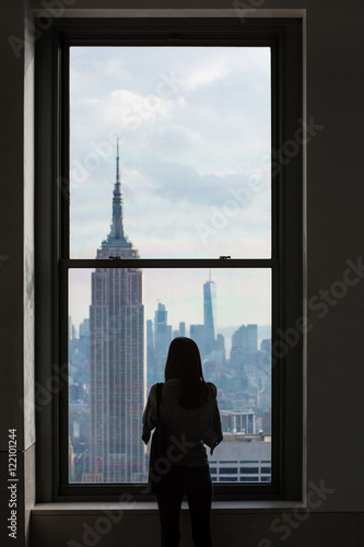 Papiers peints New York A Woman Looks out Over Downtown Manhattan Skyline with the Empire State Building, New York City