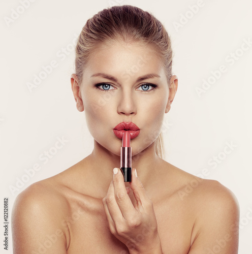 Studio portrait of young beautiful woman with perfect lips and skin holding red lipstick Poster