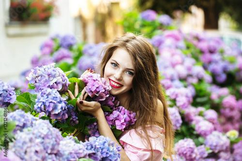 pretty smiling girl in hydrangea flowers