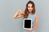 Cheerful young woman holding and pointing on blank screen tablet