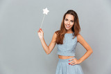 Cheerful beautiful young woman holding magic wand
