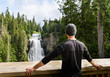 Traveler man in green forest enjoying amazing waterfall inspirational landscape. Travel, fitness and healthy lifestyle outdoors in summer nature. Alexander falls British Columbia Canada