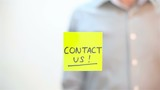 Contact Us. A man sticks a note on transparent screen