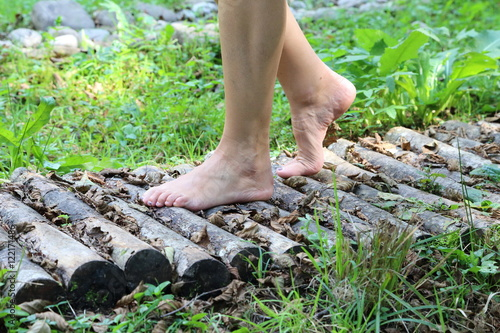 Leinwanddruck Bild woman walking barefoot in the wood