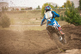 Fototapety Moto cross - MX girl biker at race in Russia - a sharp turn and the spray of dirt, rear view